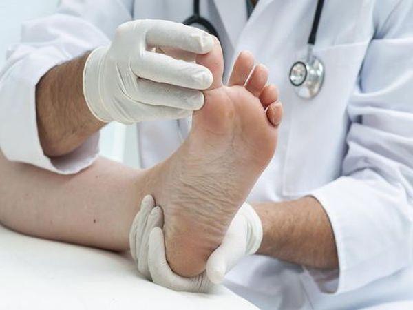 Врач осматривает пальцы ног